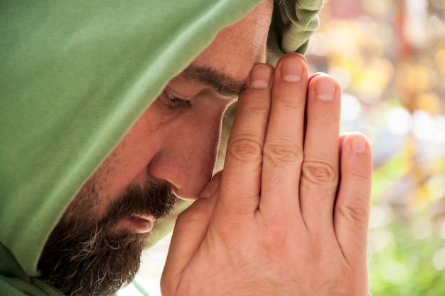 Bearded man with hoodie is praying Premium Photo