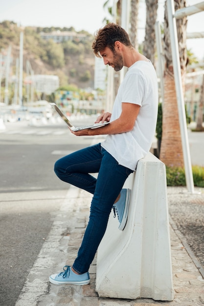 Bearded man with jeans holding a notebook Free Photo