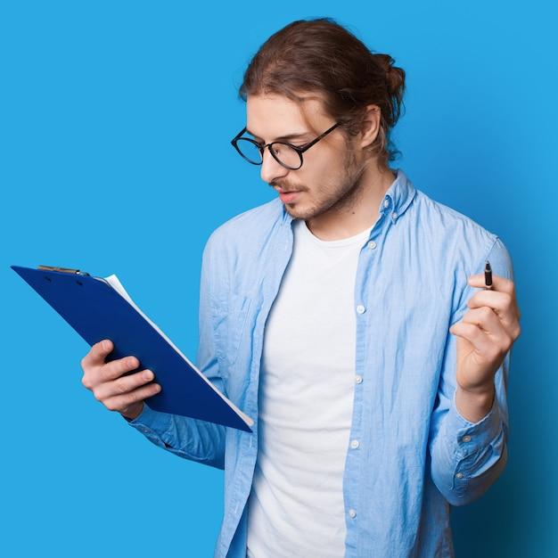 파란색 스튜디오 벽에 펜과 폴더를 들고 문서에 메모를 만드는 긴 머리를 가진 수염 난된 남자 프리미엄 사진