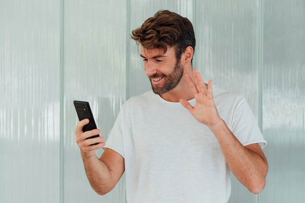Bearded man with phone waiving at camera Free Photo