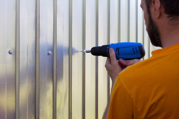A bearded man with a screwdriver in hand screwed the screws sheets metal profile Premium Photo