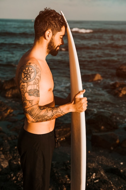 Bearded man with surf board on shore near water Free Photo