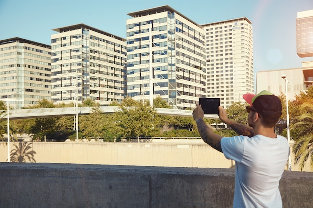 Bearded man with tattoos taking a photo of city buildings and trees Free Photo