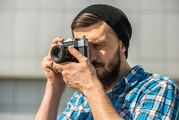 Bearded man with vintage camera is making a picture. Premium Photo