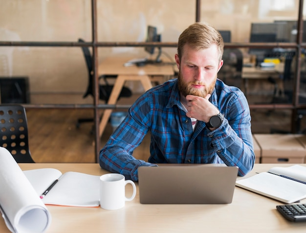Bearded man working on laptop at workplace Free Photo
