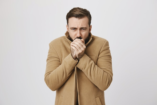 Bearded middle-aged man feeling cold on street Free Photo