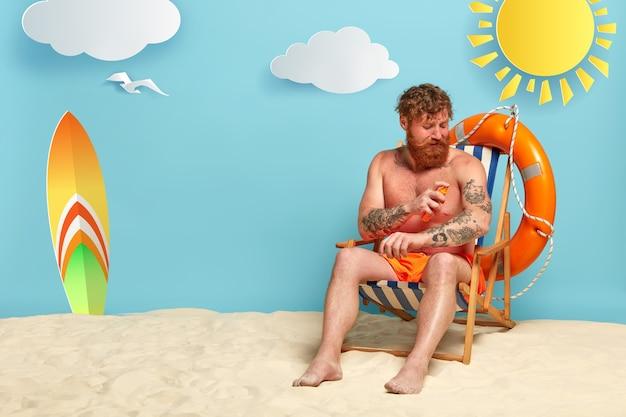 선크림과 함께 해변에서 포즈 수염 된 빨간 머리 무료 사진