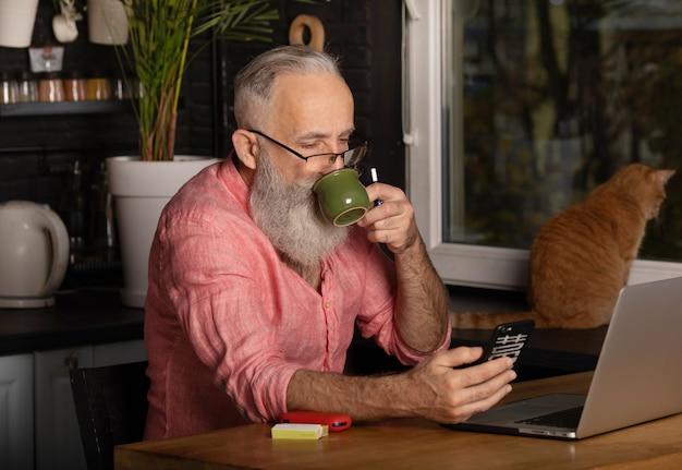 ラップトップで働くひげを生やした上級ビジネスマン Premium写真