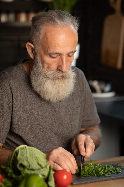 ひげを生やした年配の男性人がキッチンで健康的でおいしいサラダを準備します。 Premium写真
