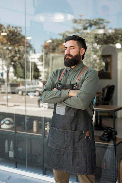 Bearded serious hairdresser standing outside near barbershop Free Photo
