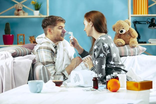 Бородатый больной мужчина и его жена сидят дома на диване, накрытые теплым одеялом, и кашляют с помощью ингалятора. Бесплатные Фотографии