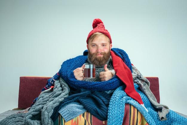 독감이 집에서 소파에 앉아 있거나 차 한잔과 함께 스튜디오에 앉아 수염 난 아픈 남자는 니트 따뜻한 옷으로 덮여 있습니다. 질병, 인플루엔자 개념. 집에서의 휴식. 의료 개념. 무료 사진
