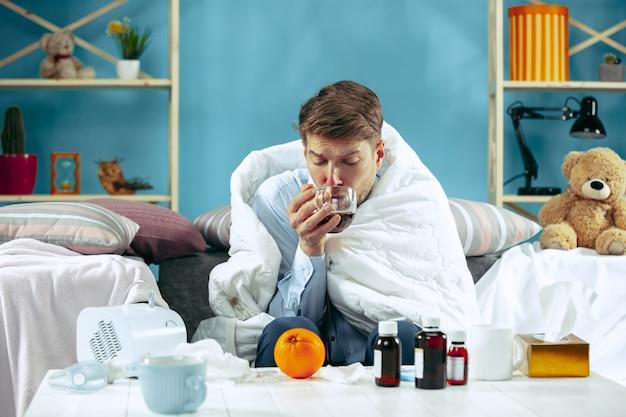Uomo barbuto malato con canna fumaria seduto sul divano a casa coperto con una coperta calda e bere sciroppo per la tosse. la malattia, l'influenza, il concetto di dolore. relax a casa Foto Gratuite