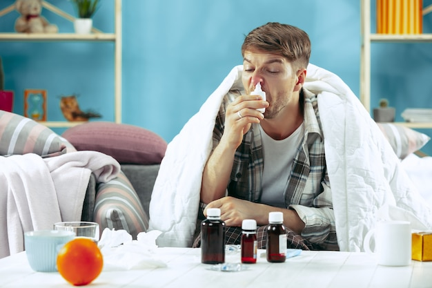 Uomo barbuto malato con canna fumaria seduto sul divano a casa coperto con una coperta calda e utilizzando spray nasale. la malattia, l'influenza, il concetto di dolore. relax a casa Foto Gratuite
