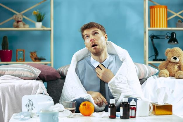 Uomo barbuto malato con canna fumaria seduto sul divano di casa e bere il tè. l'inverno, la malattia, l'influenza, il concetto di dolore. relax a casa. concetti sanitari. Foto Gratuite