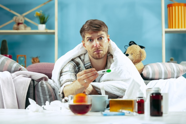 Uomo barbuto malato con canna fumaria seduto sul divano a casa e misurazione della temperatura corporea. l'inverno, la malattia, l'influenza, il concetto di dolore. relax a casa Foto Gratuite