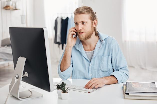 Il giovane uomo d'affari biondo e barbuto esperto lavora al nuovo progetto, si siede davanti allo schermo, ha conversazione telefonica, discute la relazione finanziaria con il businesspartner. l'impiegato chiacchiera con il capo Foto Gratuite