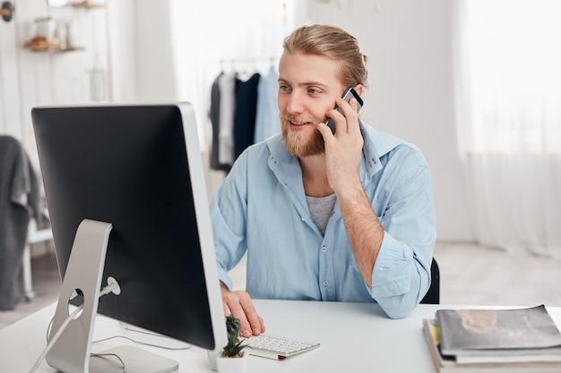 Il giovane e abile copywriter biondo con la barba lavora su un nuovo articolo, digita sulla tastiera, parla al telefono, discute il nuovo progetto con businesspartner. il riuscito uomo d'affari ha una chiamata importante. Foto Gratuite