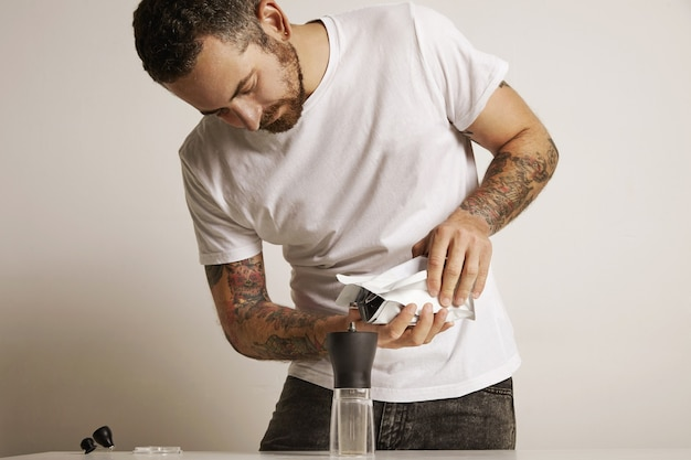 Bearded and tattooed man pouring coffee grounds into a modern manual coffee grinder from a white foiled bag Free Photo