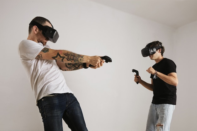 A bearded tattooed man in a white t-shirt hits a younger man in a black t-shirt in a vr game Free Photo