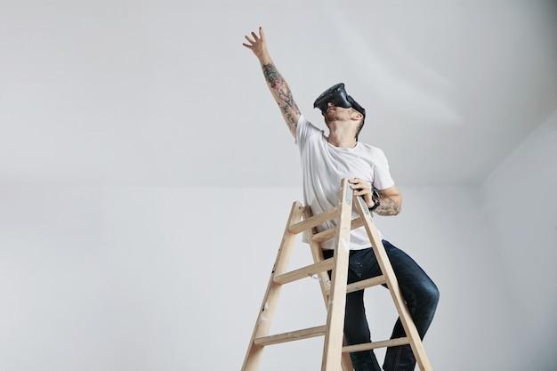 Un giovane barbuto e tatuato con una t-shirt bianca senza etichetta e occhiali vr in piedi sulla scala e che cerca qualcosa Foto Gratuite