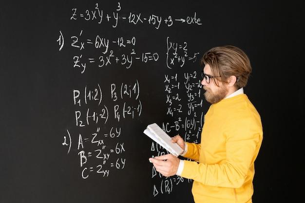 Бородатый учитель в повседневной одежде переписывает формулы на доске из своей тетради перед тем, как дать задание своей онлайн-аудитории Premium Фотографии