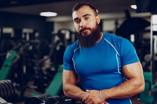 Бородатый молодой человек культурист в синей футболке, стоя в тренажерном зале Premium Фотографии