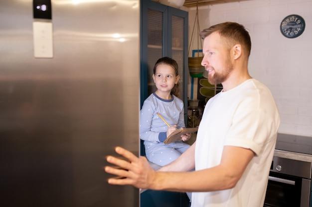 메모장과 연필로 무엇을 구입 해야할지 목록을 만드는 그의 귀여운 딸 동안 냉장고의 수염 난 젊은이 여는 문 프리미엄 사진