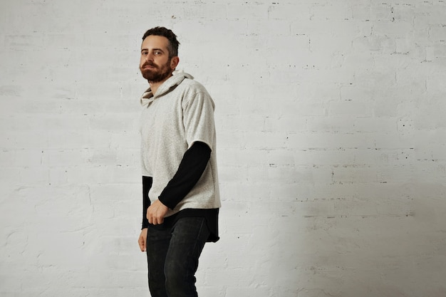 A bearded young man presenting a soft cotton plain gray sweatshirt with black jeans isolated on white Free Photo