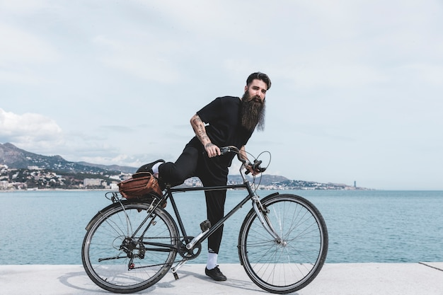 Bearded young man sitting on bicycle near the coast Free Photo