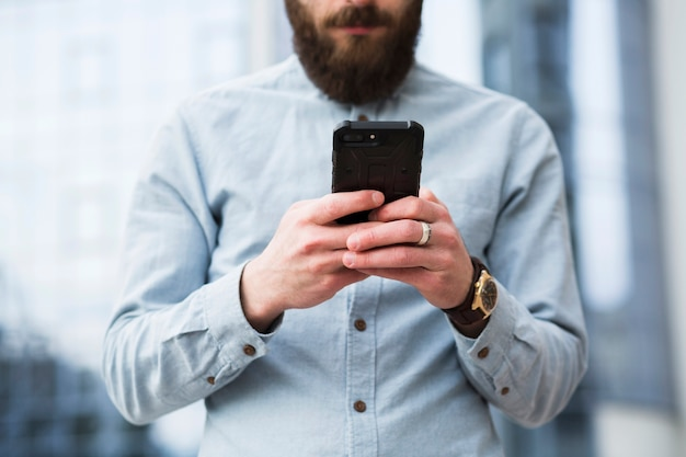 Bearded young man text messaging on mobile phone Free Photo