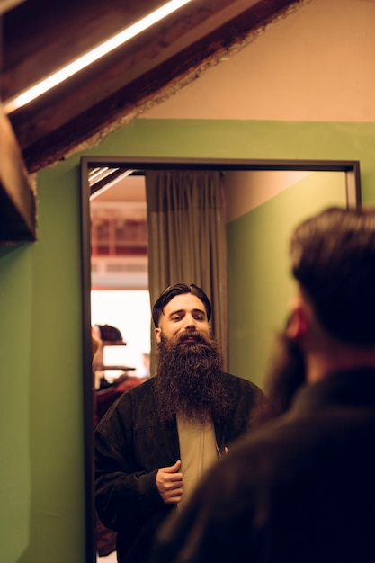Bearded young man trying jacket in front of mirror Free Photo