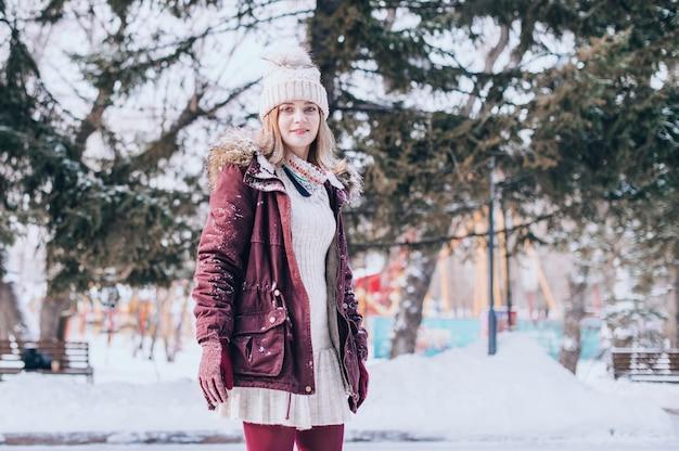 美しい女性の笑顔の肖像画。雪の冬の服を着て幸せな女の子の肖像画 Premium写真
