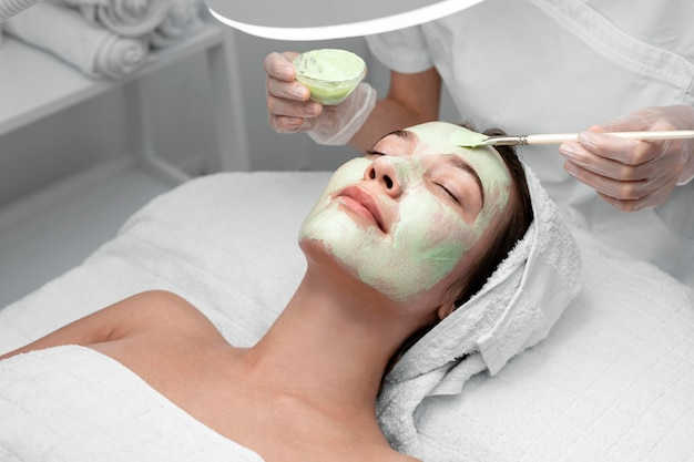 Beautician applying face mask on female client Free Photo