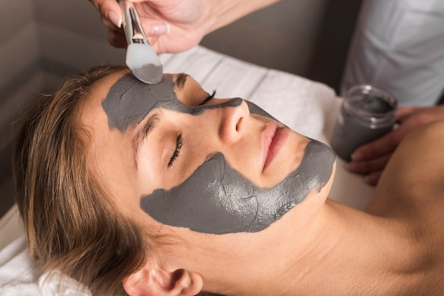 Beautician applying face mask on young woman's face Free Photo