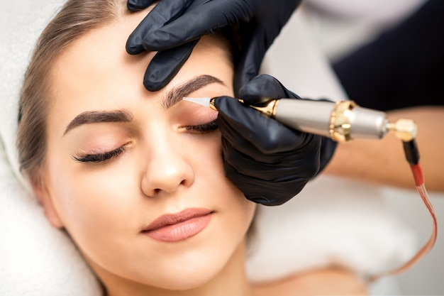 Premium Photo | Beautician applying permanent makeup on ...