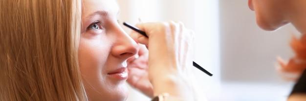 Косметолог рисует модельные брови на лице модели Premium Фотографии