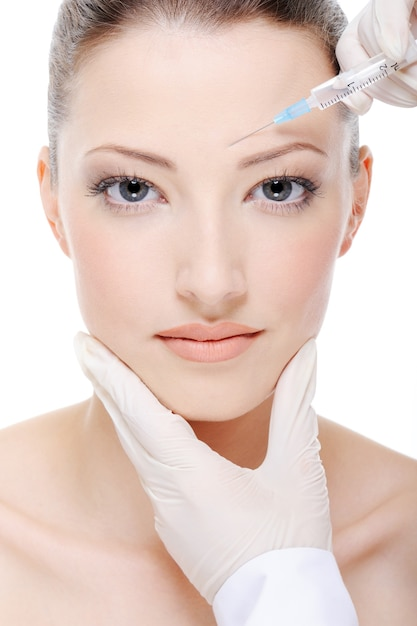 Beautician giving an injection on the young female face Free Photo