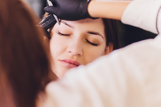 Beautician- makeup artist applies paint henna on previously plucked, design, trimmed eyebrows in a beauty salon in the session correction. professional care for face. Premium Photo
