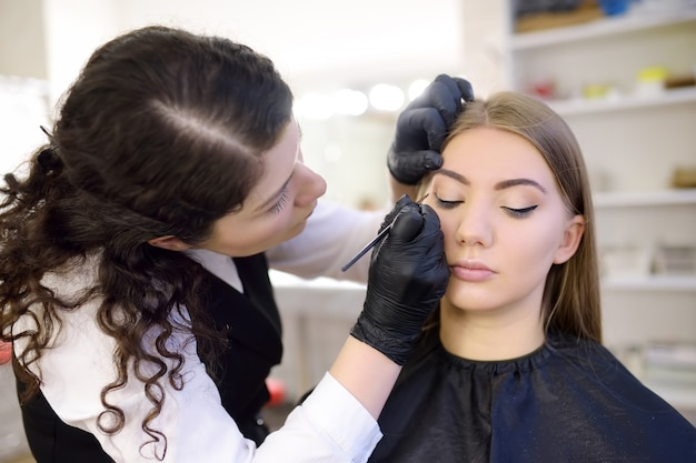 Косметолог рисует реснички глаз кистью. привлекательная женщина, получать уход за лицом и макияж в салоне красоты. архитектура бровей. Premium Фотографии