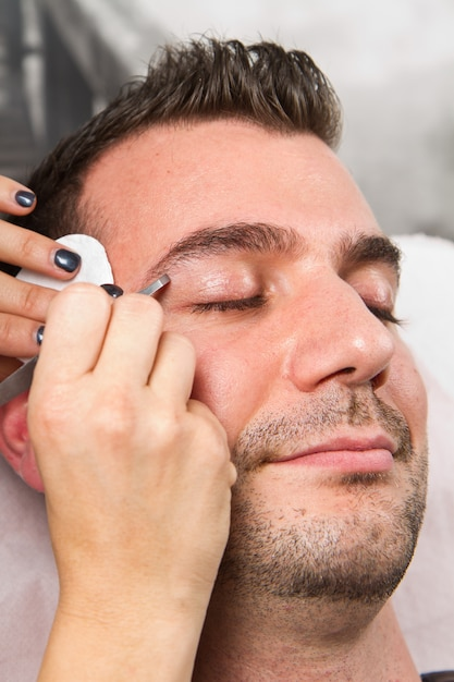 Beautician plucking a beautiful man eyebrows with tweezers in a beauty salon Premium Photo