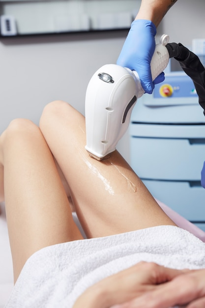 Beautician removing hair of young woman' s leg with laser Premium Photo