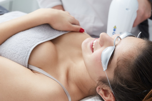 Beautician removing hair of young woman with laser Premium Photo