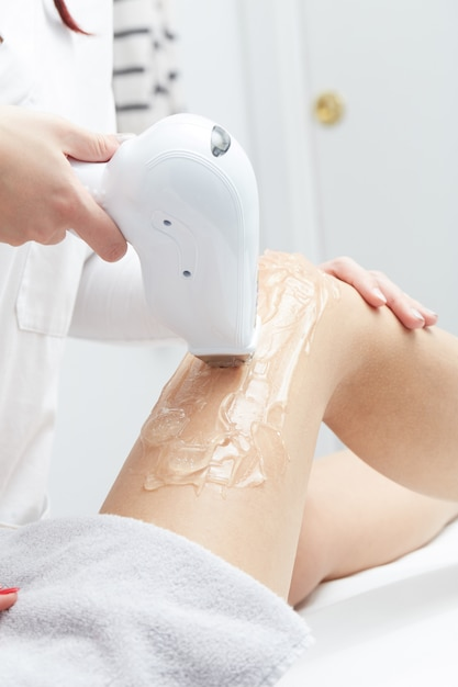 Beautician removing hair of young woman's leg with laser Premium Photo