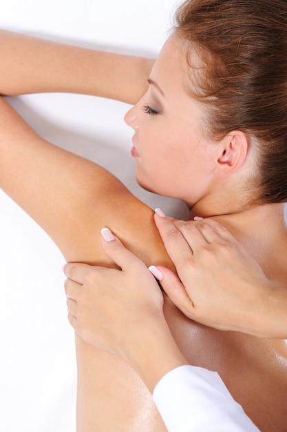 Le mani dell'estetista che danno alla giovane donna un massaggio sulla sua spalla Foto Gratuite