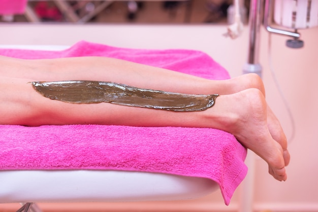Beautician waxing woman legs, depilation in beauty spa. Premium Photo