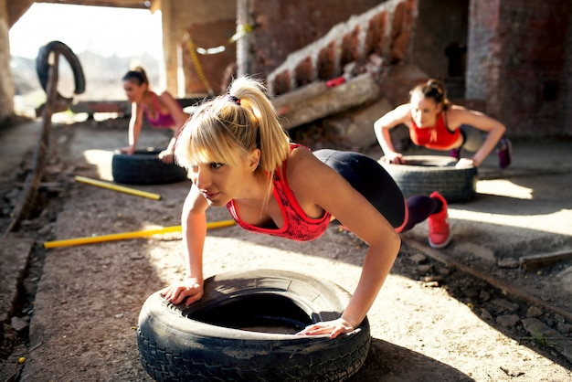 Beautiful active girls are doing push ups on tires in the old hangar. Premium Photo