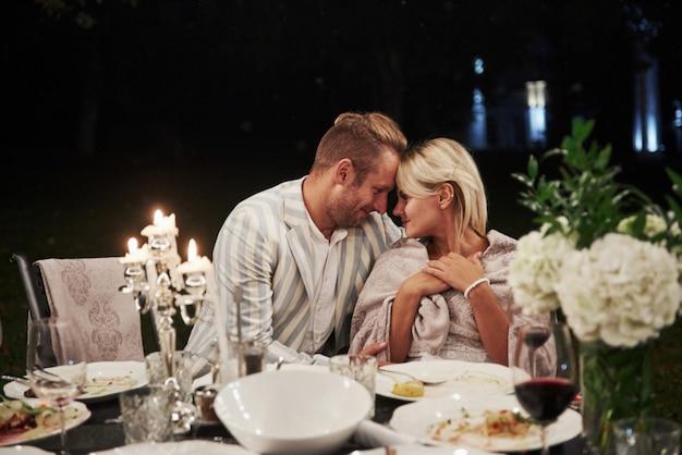 美しい大人のカップルは夜の時間に豪華なディナーを持っています 無料写真