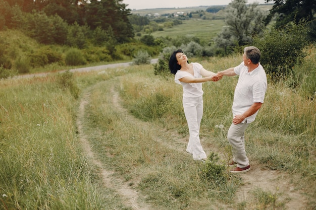 Beautiful adult couple spends time in a summer field Free Photo