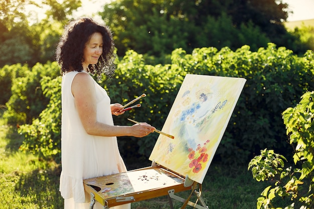 Beautiful adult woman drawing in a summer field Free Photo